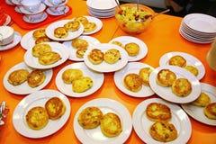 Russische pannekoek Sunny Browns en fruitsalade Op de witte porseleinplaten en de oranje tafelkleden Royalty-vrije Stock Fotografie