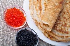 Russische Pfannkuchen - Blini mit rotem und schwarzem Kaviar Lizenzfreies Stockfoto