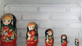 Russische Puppen mit weißer Backsteinmauer Lizenzfreie Stockfotos
