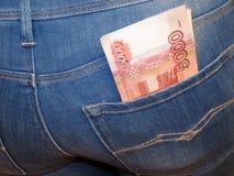 Russische roebelbankbiljetten in de zak van vrouwen` s jeans stock fotografie