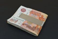 Russische roebels met klemmen Metaalklemmen met Russische vijf duizendenroebels stock foto's
