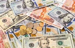 Russische roebelsmuntstukken en Amerikaanse dollars bankbiljetten Stock Foto's