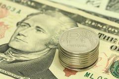 Russische Rubel auf Hintergrund von zehn Dollar Stockfotos