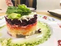 Russische salade 'haringen onder een bontjas 'heerlijke smakelijke purple van bieten en vissen op een plaat op de lijst in een ko stock afbeeldingen