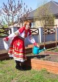 Russische Schönheit in den nationalen sundress an einem sonnigen Frühlingstag Lizenzfreie Stockbilder