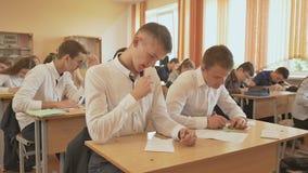 Russische school De leerlingen schrijven een controleexamen in hun notitieboekjes stock videobeelden