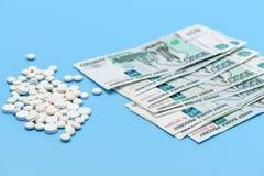Russische tausend Rubel und wei?e Pillen der Runde auf einem blauen Hintergrund stockfotografie