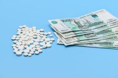 Russische tausend Rubel und wei?e Pillen der Runde auf einem blauen Hintergrund stockbilder