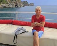 Russische toerist tegen de achtergrond van overzees en rotsen Stock Fotografie