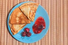 Russische traditionelle Tellerpfannkuchen mit Kirschen, Stau und Milch Stockbild