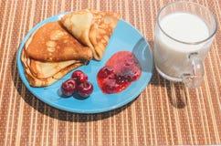 Russische traditionelle Tellerpfannkuchen mit Kirschen, Stau und Milch Stockbilder