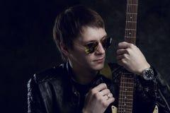 Russische Tuimelschakelaar De kerel met de gitaar voor een fotograaf Grungemuziek, koorden, muziek, instrument, gitaar, spiritual Royalty-vrije Stock Afbeelding
