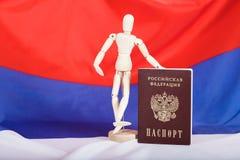 Russischer Durchlauf und hölzerne blinde Figürchen auf russischer Flagge Stockbilder