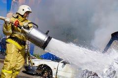 Russischer Feuerwehrmann setzt heraus ein Feuer, einen großen Jet des weißen Schaums, Hydrant, die Auslöschung, episch stockfotografie