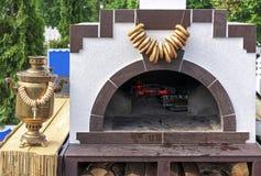 Russischer hölzerner Ofen und antiker Samowar mit Bündeln Bageln lizenzfreies stockbild