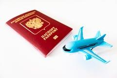 Russischer internationaler Pass und eine blaue Fläche auf weißem Hintergrund Reise, Reise und fliegendes Konzept stockfotografie