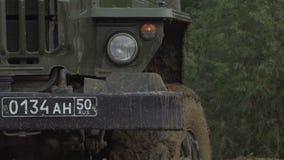 Russischer LKW des Armee-Personals, der auf Schotterweg fährt Schmutziges gepanzertes Fahrzeug stock video footage
