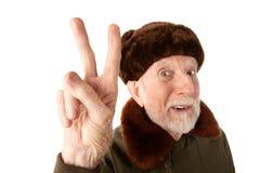 Russischer Mann in der Pelz-Schutzkappe, die Friedenszeichen bildet Stockbild