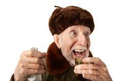 Russischer Mann in der Pelz-Schutzkappe mit Wodka stockfoto