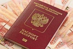 Russischer Pass auf dem Hintergrund des russischen Geldes Stockbilder