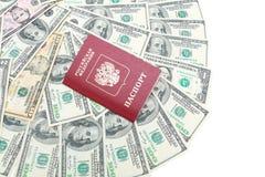 Russischer Pass auf einem Hintergrund von US-Dollar auf einer Weißrückseite Stockbilder