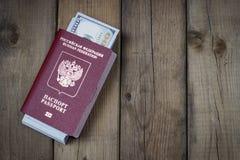 Russischer Pass mit Dollar nach innen auf hölzernem Hintergrund, Konzept der Immigration stockfoto