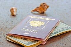 Russischer Pass mit einem Dollar investiert und Seashells Stockfoto