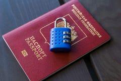 Russischer Pass zugeschlossen zum Vorhängeschloß Symbol von anti-russischen Sanktionen lizenzfreie stockfotos