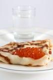 Russischer Pfannkuchen mit rotem Kaviar und Wodka Stockfotos