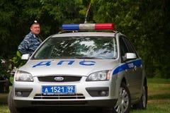 Russischer Polizeibeamte mit einem Polizeiwagen Lizenzfreie Stockfotografie