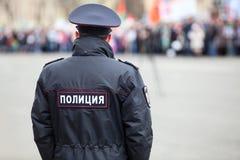 Russischer Polizistoffizier steht zur gegenüberliegenden Menge mit Aufschrift Polizei auf einheitlicher Jacke, Russland, Kopienra Stockbild
