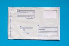 Russischer Postenpoly?thylenumschlag auf blauem Hintergrund Plastikverschickende Posttaschen lizenzfreies stockfoto
