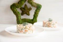 Russischer Salat auf einer weißen Platte lizenzfreies stockfoto