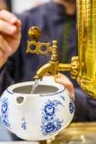 Russischer Samowar Goss das kochende Wasser in die Teekanne für Br Lizenzfreie Stockfotos