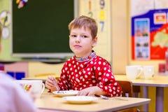 Russischer sechs Jährigjunge im roten Hemd essend im Kindergarten, unscharfer Hintergrund stockfoto