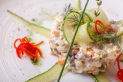Russischer traditioneller Salat Olivier mit Gemüse und Fleisch Salat auf einem weißen Teller auf Tabelle Hochzeitsabendessen mit  stockfoto