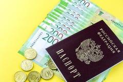Russisches Bargeld und einige Münzen Bezeichnungen in 200 Rubeln Russischer Pass auf einem gelben Hintergrund Lizenzfreie Stockfotografie
