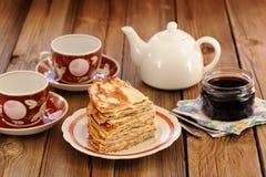 Russisches bliny mit Korinthenmarmelade, Teeschalen, Topf auf hölzernem backgrou Stockbilder