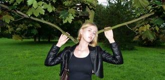 Russisches blondes Mädchen, das nahe dem Baum in der Jacke aufwirft Lizenzfreie Stockbilder