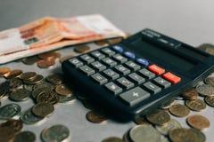 Russisches Geld, Münzen und Banknoten, Taschenrechner auf dem grauen Hintergrund lizenzfreies stockbild
