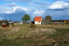 Russisches Landschaftsdorf und -straße Himmel mit schönen Wolken Stockfotografie
