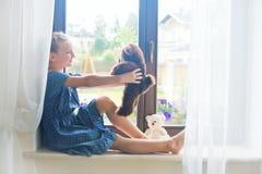 Russisches Mädchen des einsamen Kleinkindes, das zu Hause auf Schwelle nahe Fenster sitzt Lizenzfreies Stockbild