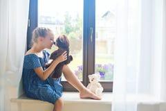 Russisches Mädchen des einsamen Kleinkindes, das zu Hause auf Schwelle nahe Fenster sitzt stockfoto