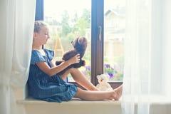 Russisches Mädchen des einsamen Kleinkindes, das zu Hause nahe dem spielenden Fenster sitzt Stockbilder