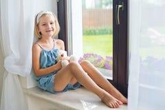 Russisches Mädchen des einsamen Kleinkindes, das zu Hause nahe dem spielenden Fenster sitzt lizenzfreie stockfotografie