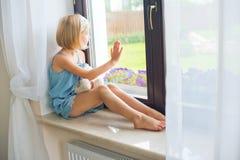 Russisches Mädchen des einsamen Kleinkindes, das zu Hause nahe dem spielenden Fenster sitzt lizenzfreies stockbild