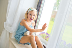 Russisches Mädchen des einsamen Kleinkindes, das zu Hause nahe dem spielenden Fenster sitzt stockfoto