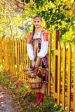 Russisches Mädchen in einer Klage, die einen Korb der Apfelernte hält Lizenzfreie Stockfotos
