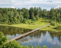 Russisches Norddorf Isady Sommertag, Emca-Fluss, alte Häuschen auf dem Ufer, alte Holzbrücke und Wolkenreflexionen Stockbild
