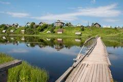 Russisches Norddorf Isady Sommertag, Emca-Fluss, alte Häuschen auf dem Ufer, alte Holzbrücke und Wolkenreflexionen Lizenzfreie Stockfotos